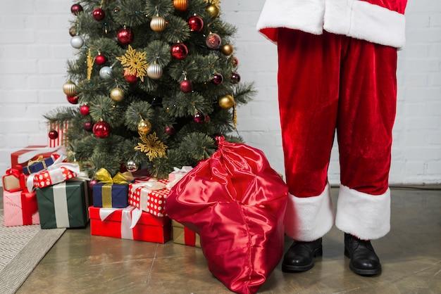 mensch in sankt anzug in der n he von weihnachtsbaum. Black Bedroom Furniture Sets. Home Design Ideas