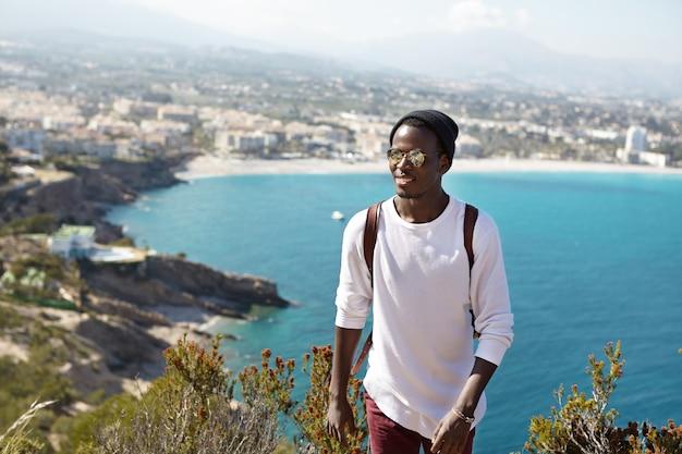 Menschen, aktiver lebensstil, reisen, abenteuer und tourismuskonzept. hübscher trendiger aussehender afroamerikanischer tourist mit rucksack, der urlaub im ausland verbringt Kostenlose Fotos