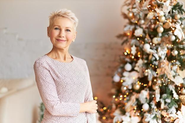 Menschen, alter, lebensstil, freude, glück und festliche stimmung konzept. modische sechzigjährige blonde dame im feiertagskleid, das neujahr feiert, glücklichen gesichtsausdruck habend, der am weihnachtsbaum aufwirft Kostenlose Fotos