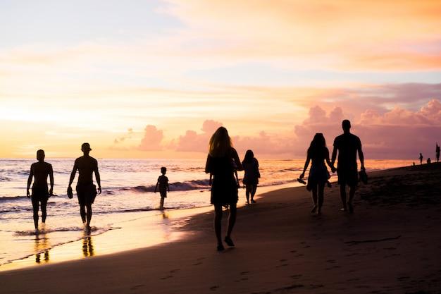 Menschen am strand bei sonnenuntergang. Kostenlose Fotos
