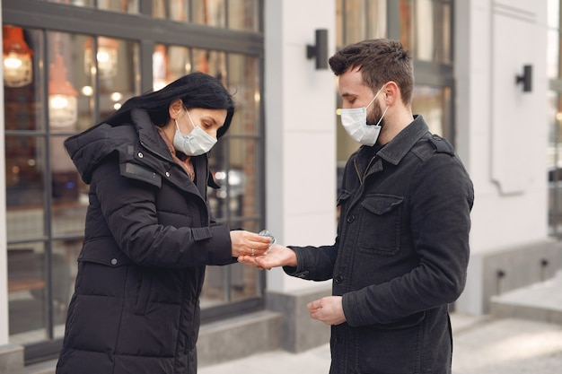 Menschen, die eine schutzmaske tragen, stehen auf der straße, während sie alkoholgel verwenden Kostenlose Fotos
