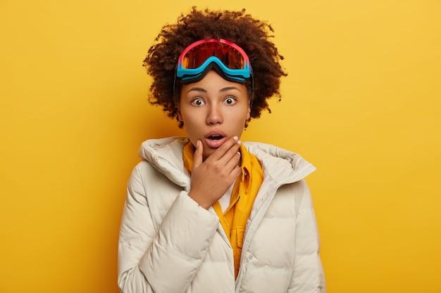 Menschen, emotionen, hobby und freizeitkonzept. verängstigte emotionale lockige afroamerikanerin trägt snowboardmaske, gekleidet in geschwollenen weißen mantel, hält kinn Kostenlose Fotos