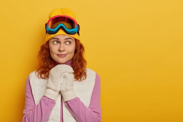 Menschen, erholung, gedanken, freizeitaktivitäten konzept. die entzückende ingwerfrau hält die hände über der brust zusammen, trägt ein warmes outfit, eine snowboardmaske und denkt über neue abenteuer im winter nach Kostenlose Fotos
