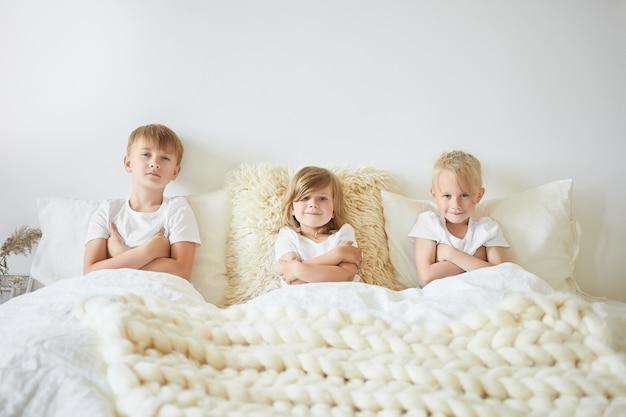 Menschen-, familien- und kindheitskonzept. drei kinder sitzen nebeneinander auf einem großen weißen bett mit verschränkten armen und schauen sich am wochenendmorgen cartoons an. zwei brüder und schwestern spielen zu hause Kostenlose Fotos