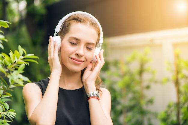 Menschen freizeit-und technologie-konzept - attraktive junge frau musik hören auf dem musik-player im freien. hipster mädchen genießen die melodien in ihren kopfhörern in den morgen park. objektiv flare. Kostenlose Fotos