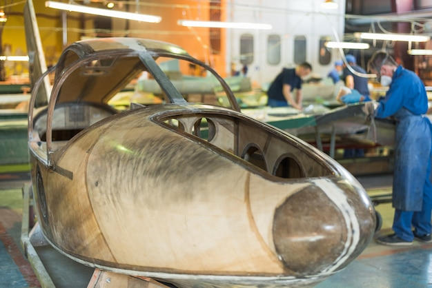 Menschen in blauen gewändern bauen in der fabrik ein flugzeug. arbeiter in overalls arbeiten an den details des flugzeugs. Premium Fotos