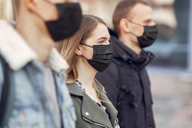 Menschen in masken stehen auf der straße Kostenlose Fotos