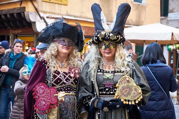 Menschen in masken und kostümen beim karneval in venedig Premium Fotos