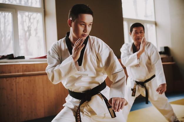 Menschen in weißen kleidern und schwarzen gürteln trainieren im fitnessstudio Premium Fotos