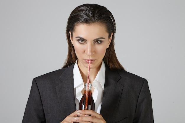 Menschen, lebensstil, lebensmittel- und getränkekonzept. bild der ernsthaften durstigen geschäftsfrau gekleidet in übergroßen männerkleidern, die isolierte haltende glasflasche darstellen, braunes soda gedankenstroh nippend Kostenlose Fotos