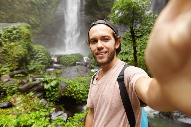 Menschen-, lifestyle-, natur- und abenteuerkonzept. stilvoller junger reisender mit rucksack, der selfie im regenwald mit wasserfall nimmt Kostenlose Fotos