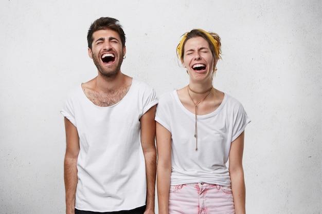 Menschen, mimik und körpersprachenkonzept. junge frau und ihr freund lachen mit weit geöffnetem mund und geschlossenen augen Kostenlose Fotos