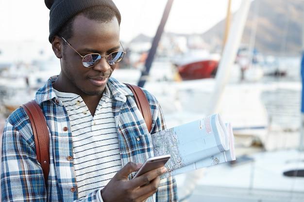 Menschen, moderne technologie, kommunikation, reisen und tourismuskonzept. hübscher junger afroamerikanischer rucksacktourist mit papierkarte und handy, nachrichten online, während gerade in der neuen stadt angekommen Kostenlose Fotos