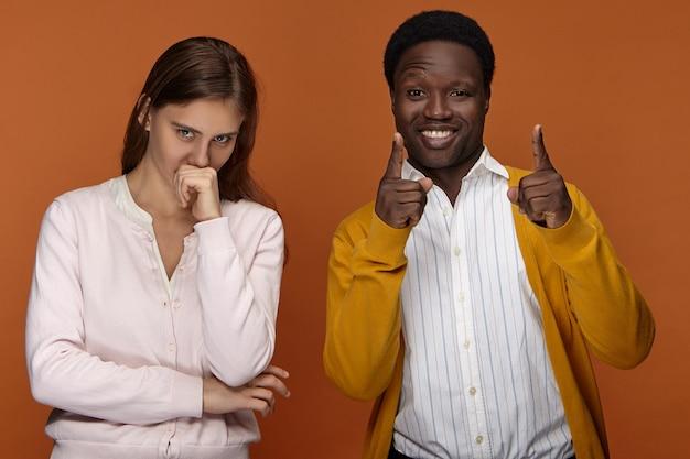 Menschen, rasse und ethnische zugehörigkeit. glücklicher aufgeregter junger afroamerikanischer kerl in guter laune, der freudig lächelt, zeigefinger zeigt, niedliches langhaariges europäisches mädchen, das faust an ihrem mund hält und lacht Kostenlose Fotos
