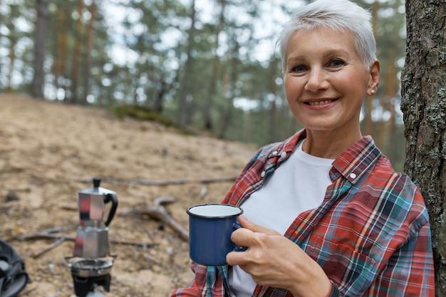 Menschen, reisen, wandern und urlaub. freudige kaukasische frau mittleren alters, die draußen mit tasse aufwirft, tee in der wilden natur trinkend, auf campingplatz im kiefernwald ruhend genießt, friedliche atmosphäre genießt Kostenlose Fotos