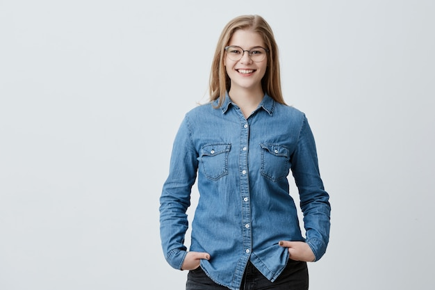 Menschen-, schönheits- und lifestyle-konzept. attraktive sinnliche blonde frau mit brille und breitem lächeln gekleidet in jeanshemd lächelnd breit glücklich, ihre beste freundin zu treffen. freudige nette frau Kostenlose Fotos