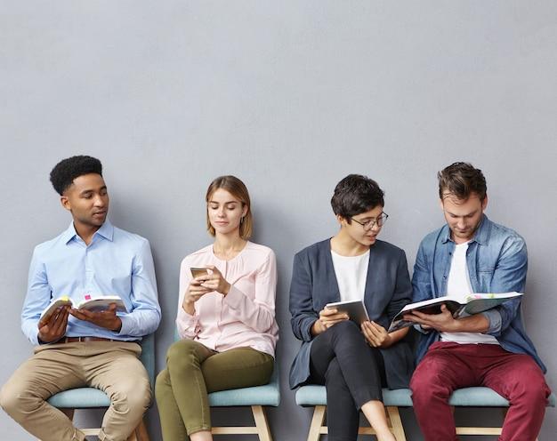 Menschen sitzen nebeneinander auf stühlen Kostenlose Fotos