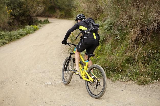 Menschen, sport, extrem, risiko und aktives konzept für einen gesunden lebensstil. junger europäischer männlicher radfahrer, der fahrradkleidung und schutzausrüstung trägt, die gelbes mountainbike schnell entlang spur im wald reitet Kostenlose Fotos