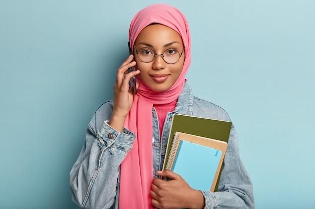 Menschen, technologie, ethnische zugehörigkeit, kommunikationskonzept. hübsches mädchen im traditionellen muslimischen hijab hat telefongespräch mit gruppenmitglied, bespricht zukünftiges projekt, hält zwei spiralblöcke, posiert drinnen Kostenlose Fotos