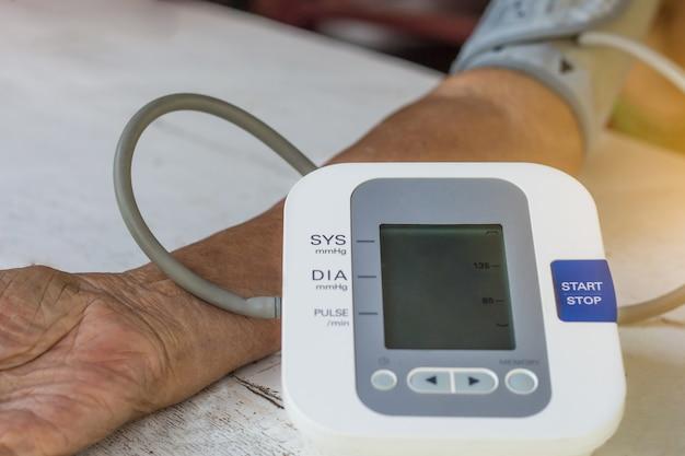 Menschen überprüfen blutdruckmessgerät und herzfrequenzmessgerät mit digitalem druck Premium Fotos