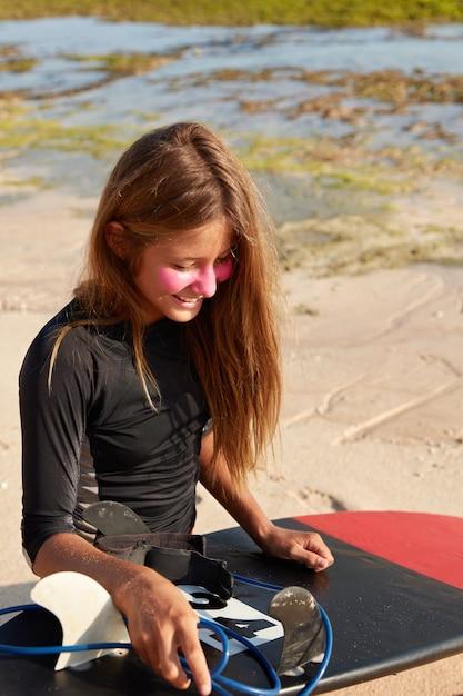 Menschen- und ruhekonzept. vertikaler schuss des fröhlichen surfboarders im schwarzen neoprenanzug Kostenlose Fotos