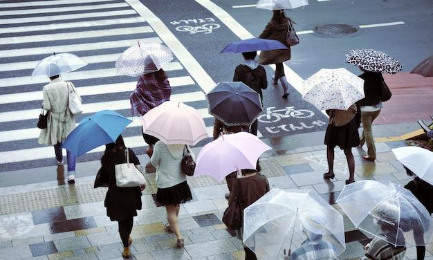 Menschen unter regenschirmen am zebrastreifen in tokio Premium Fotos