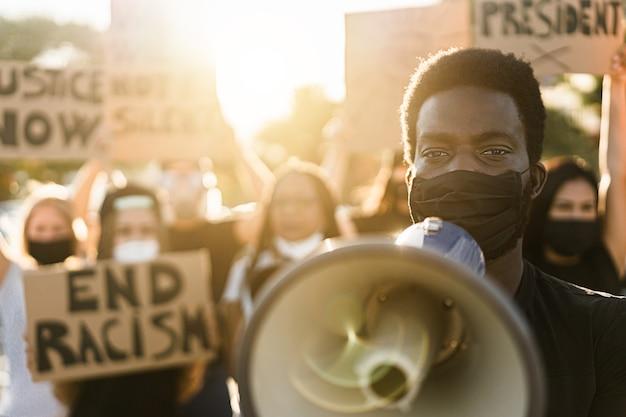 Menschen unterschiedlicher kulturen und rassen protestieren auf der straße für gleichberechtigung - demonstranten, die während der kampfkampagne gegen schwarze leben gesichtsmasken tragen - fokus auf augen schwarzer männer Premium Fotos
