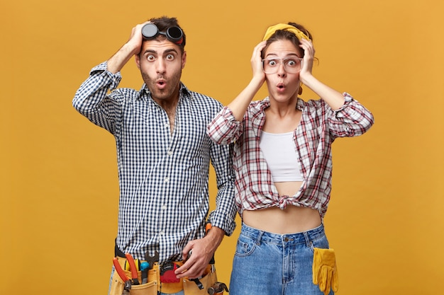 Menschliche emotionen und gefühle. zwei überraschte, erstaunte junge kaukasische servicetechniker, die eine schutzbrille und einen overall trugen, die erstaunt und schockiert aussahen und hände auf dem kopf hielten Kostenlose Fotos