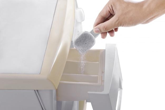 Menschliche hände geben das waschmittel in die waschmaschine Premium Fotos