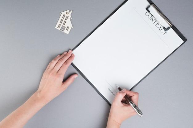 Menschliche hand, die auf vertragspapier nahe papierhausausschnitt über grauem hintergrund unterzeichnet Kostenlose Fotos