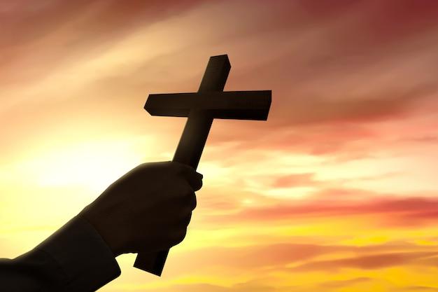 Menschliche hand, die christliches kreuz hält Premium Fotos