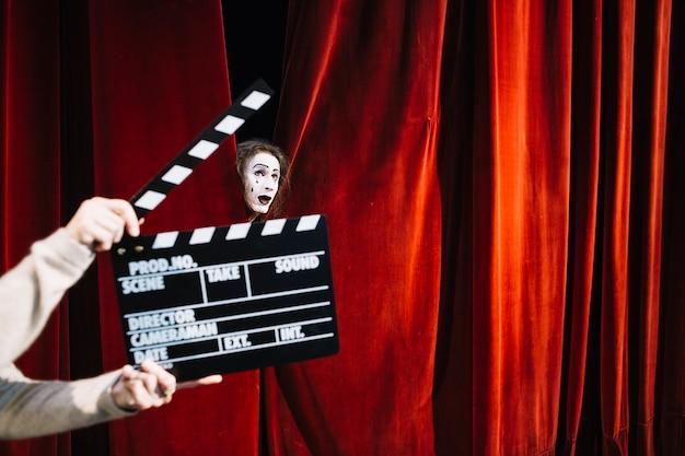 Menschliche hand, die clapperboard vor männlichem pantomimekünstlergesicht hält Kostenlose Fotos