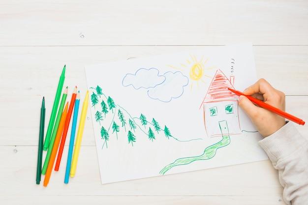 Menschliche hand, die eine hand gezeichnete zeichnung mit rotem filzstift zeichnet Kostenlose Fotos