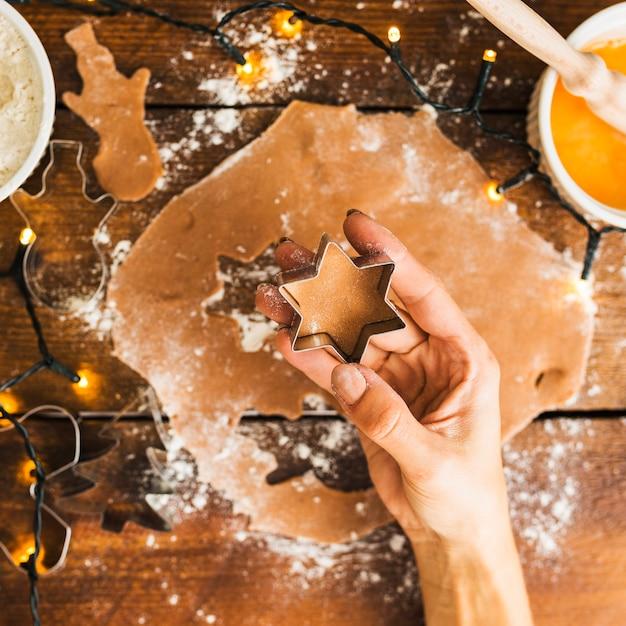 Menschliche hand, die form für keks hält Kostenlose Fotos