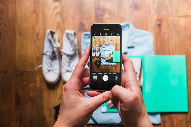 Menschliche hand, die foto des persönlichen zubehörs auf tabelle macht Kostenlose Fotos
