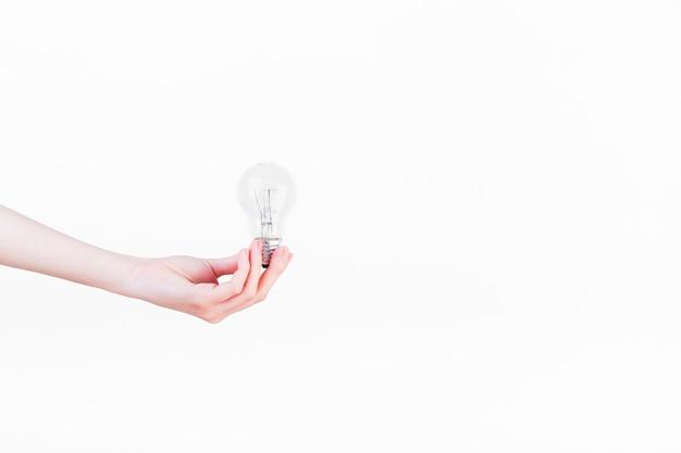 Menschliche hand, die glühlampe auf weißem hintergrund hält Kostenlose Fotos