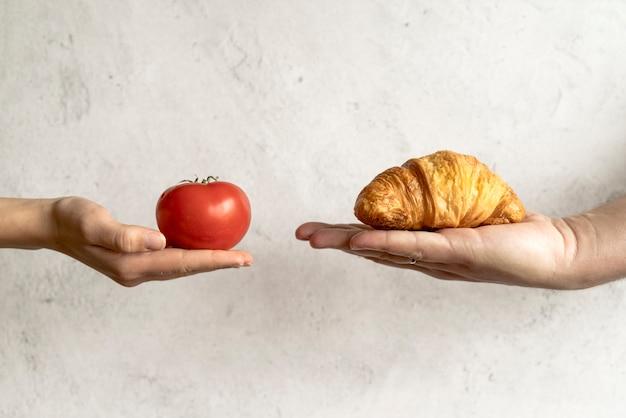 Menschliche hand, die hörnchen und rote tomate vor konkretem hintergrund zeigt Kostenlose Fotos