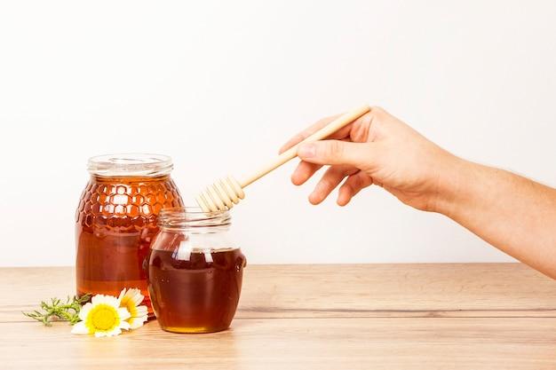 Menschliche hand, die honigschöpflöffel vom honigglas hält Kostenlose Fotos