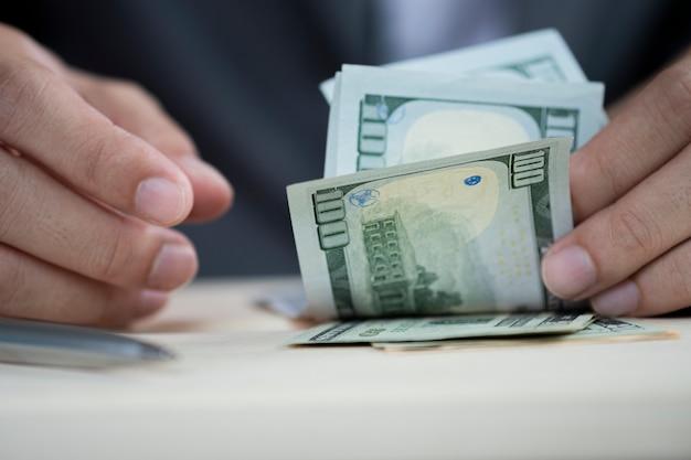 Menschliche hand, die hundert us-dollar banknote zählt. Premium Fotos