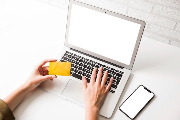 Menschliche hand, die kreditkarte hält und auf laptop mit handy schreibt Kostenlose Fotos