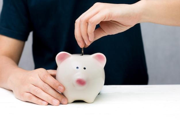 Menschliche hand, die münze in ein sparschwein setzt. einsparungskonzept. Premium Fotos