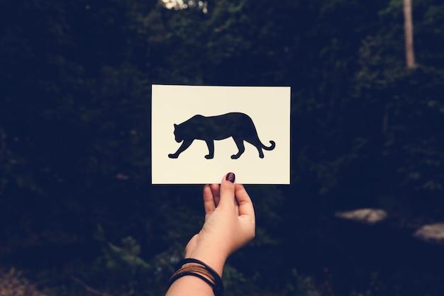 Menschliche hand, die perforiertes papierhandwerk des wilden lebenleoparden in n hält Kostenlose Fotos