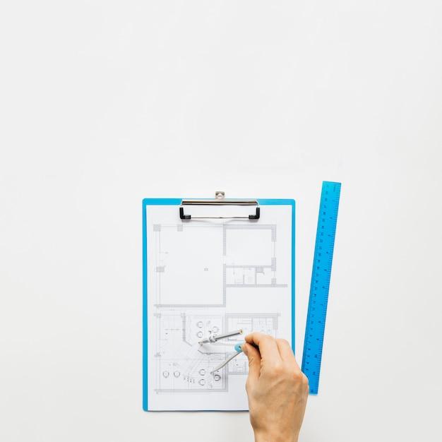 Menschliche hand, die plan unter verwendung des allrounders auf weißem schreibtisch macht Kostenlose Fotos
