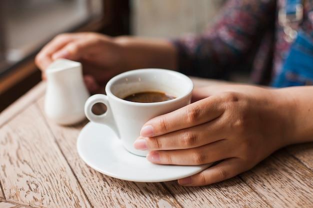 Menschliche hand, die schwarzen kaffeetasse- und milchkrug hält Kostenlose Fotos