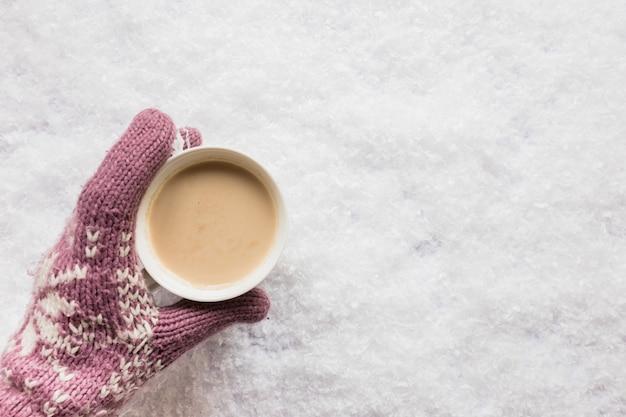 Menschliche hand, die tasse kaffee über dem schneebedeckten land hält Kostenlose Fotos