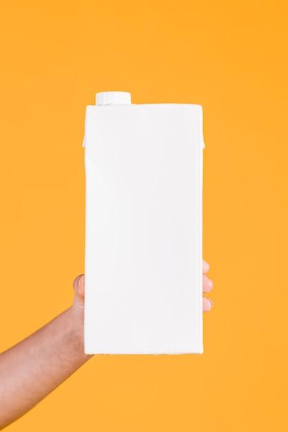Menschliche hand, die weißen milchkasten auf gelbem hintergrund anhält Kostenlose Fotos