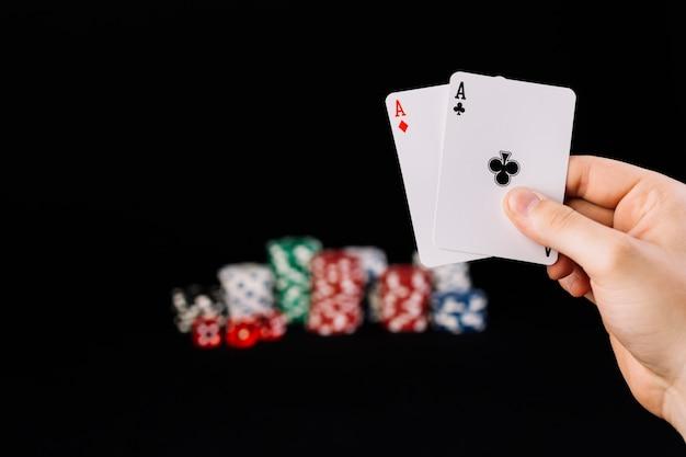 Menschliche hand, die zwei spielkarten der asse hält Kostenlose Fotos