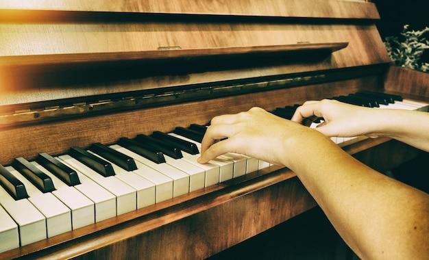 Menschliche hand drückt auf klaviertaste, warmer heller ton, verschwommenes licht herum Premium Fotos