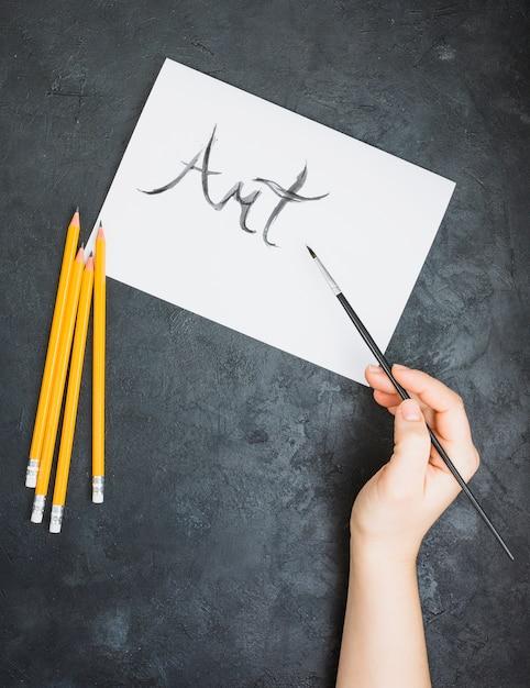 Menschliche hand schriftlicher kunsttext auf weißer seite mit pinsel über schieferoberfläche Kostenlose Fotos