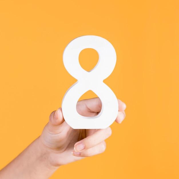 Menschliche hand, welche die weiße nr. 8 auf einem gelben hintergrund hält Kostenlose Fotos